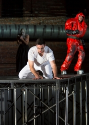 """(L-R): Yury Yanowsky as the Man (rear), Neal Ferreira as The Visitor, and David McFerrin as The Officer in Boston Lyric Opera's new """"Opera Annex"""" production of Philip Glass's dystopian """"In the Penal Colony"""" based on the Franz Kafka short story, and in a limited run Nov 11-15 at the historic Cyclorama at the Boston Center for the Arts."""