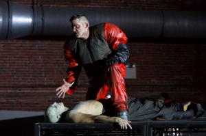 """(Top-Bottom): David McFerrin as The Officer threatens Yury Yanowsky as the Man in Boston Lyric Opera's new """"Opera Annex"""" production of Philip Glass's dystopian """"In the Penal Colony"""" based on the Franz Kafka short story, and in a limited run Nov 11-15 at the historic Cyclorama at the Boston Center for the Arts."""