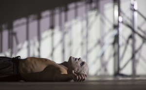 """Yury Yanowsky as the Man lay prone and exhausted in Boston Lyric Opera's new """"Opera Annex"""" production of Philip Glass's dystopian """"In the Penal Colony"""" based on the Franz Kafka short story in a limited run Nov 11-15 at the historic Cyclorama at the Boston Center for the Arts."""