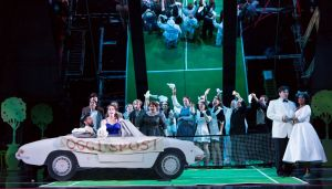 """The court bids farewell to Figaro and Susanna (in car) as the race off to a honeymoon after their wedding in Boston Lyric Opera's new production of """"The Marriage of Figaro"""" running through May 7 at John Hancock Hall"""