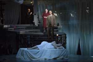 """After greeting Tarquinius and granting him shelter, Lucretia (Kelley O'Connor) sleeps while the Female Chorus and Male Chorus (Antonia Tamer and Jesse Darden) foretell her fate in Boston Lyric Opera's production of """"The Rape of Lucretia"""" March 11-17 at Artists for Humanity EpiCenter."""