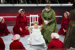 """As an Aunt (Jessica Johnson Brock) looks on, Ofwarren (Kathryn Skemp Moran) prepares for childbirth in Boston Lyric Opera's production of """"The Handmaid's Tale,"""" running through May 12. BLO.org."""