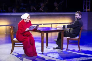 """In the Commander's office (David Cushing), Offred (Jennifer Johnson Cano) reads aloud from a beauty magazine published in the Time Before in Boston Lyric Opera's production of """"The Handmaid's Tale,"""" running through May 12. BLO.org."""