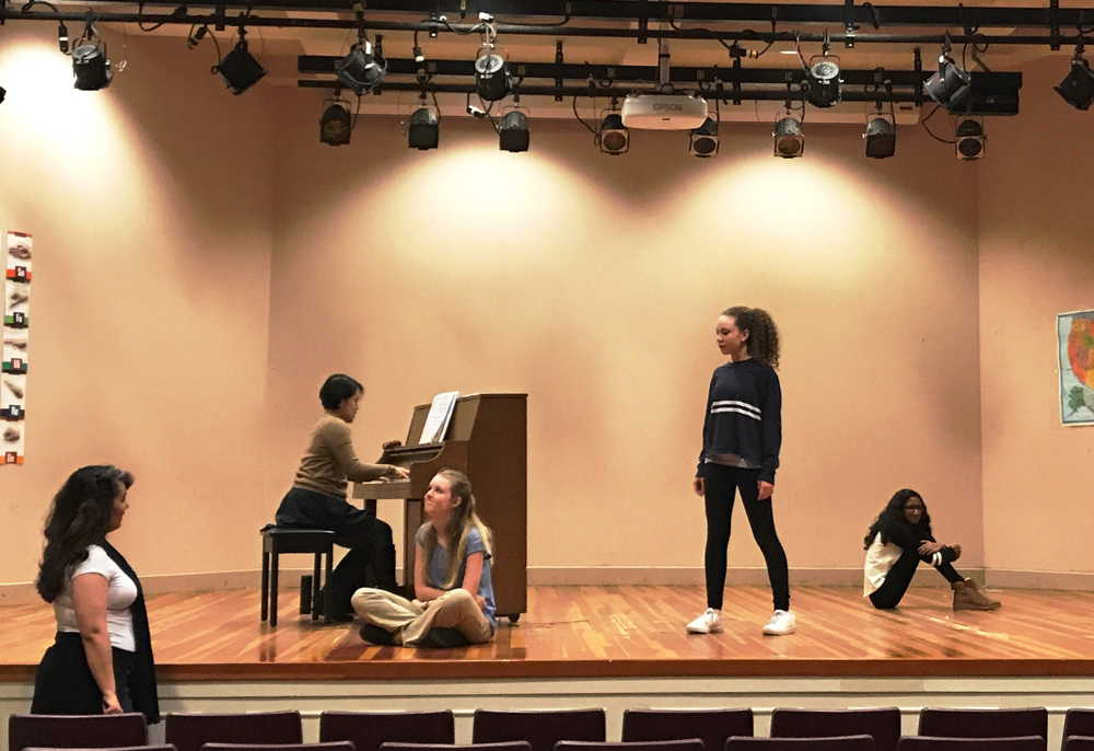 A teaching artist stands next to a stage while two students are sitting and one is standing. A second teaching artist is playing the piano. The students are being coached as part of the Middle School Audition Workshop.