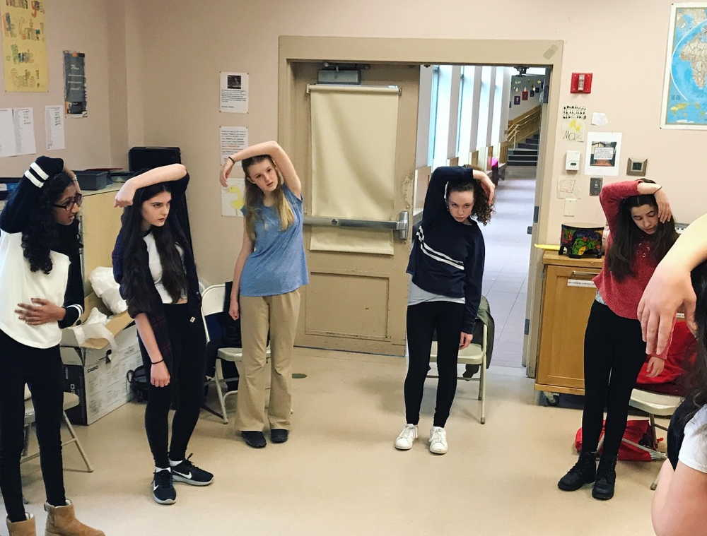 five young women stand in a circle, each with one arm stretched over their heads. Part of a warm-up exercise in the Middle School Audition Workshop.